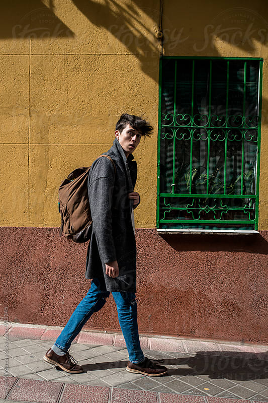 Young man carrying a backpack by Márquez Studio for Stocksy United