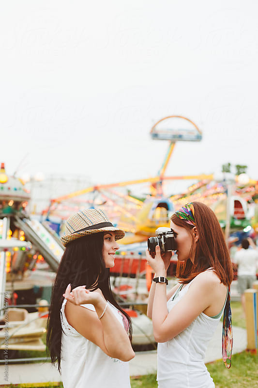 Two young woman having fun and taking photos at amusement park by Aleksandra Kovac for Stocksy United