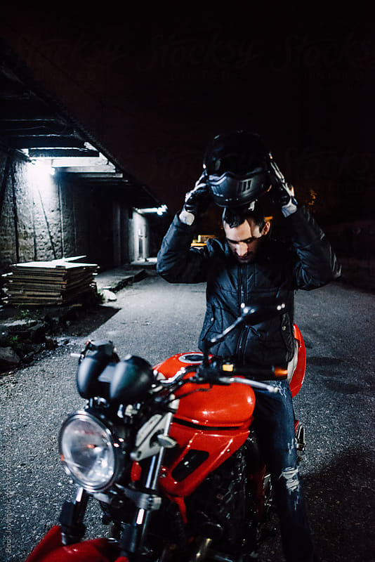 Biker setting up a helmet while sitting on his motorbike by Boris Jovanovic for Stocksy United