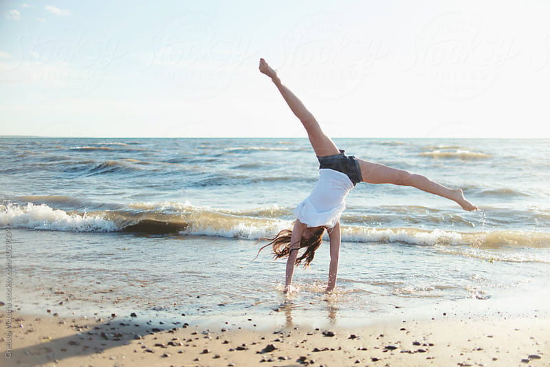 A teenage girl doing gymnastics at the beach by Chelsea Victoria for Stocksy United