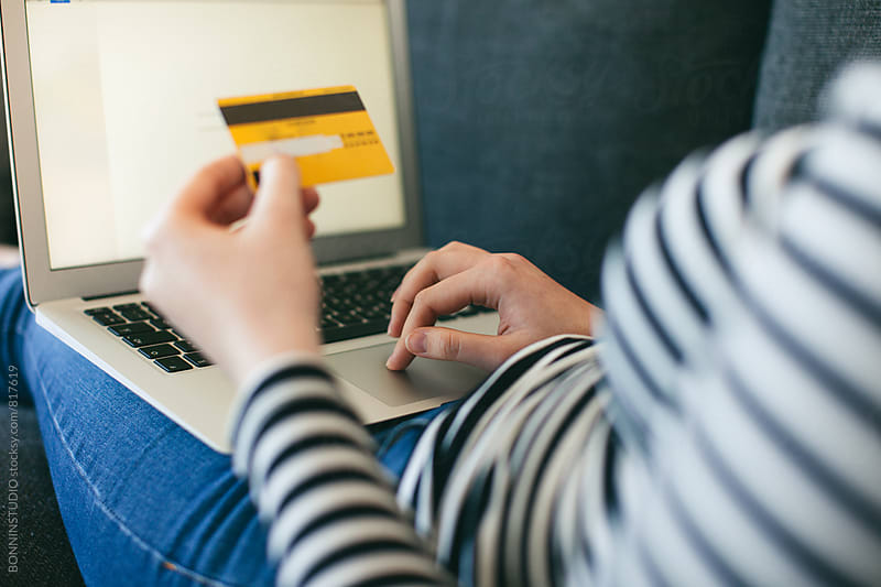 Closeup of a woman shopping online with her credit card from home. by BONNINSTUDIO for Stocksy United