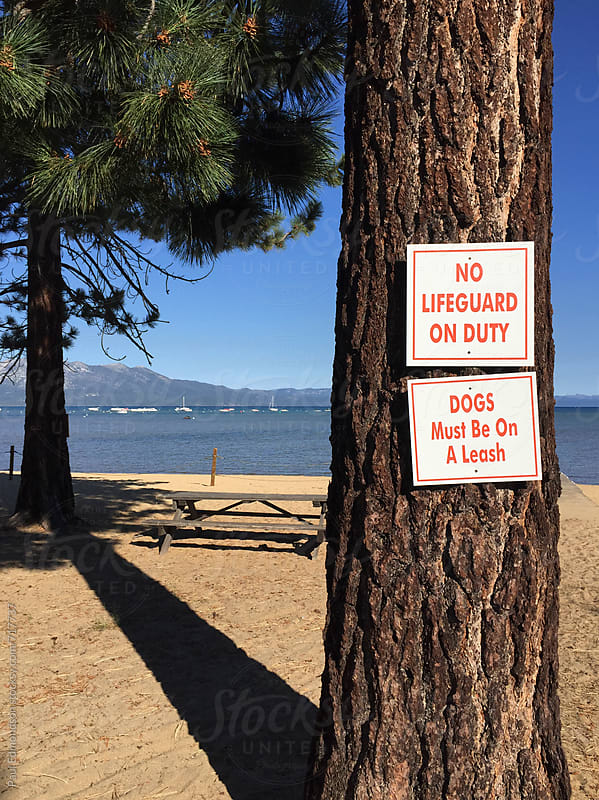 Shoreline of Lake Tahoe with caution signs by Paul Edmondson for Stocksy United