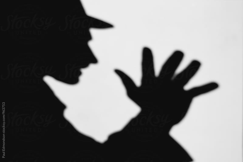Shadow of man with hand raised, wearing fedora hat by Paul Edmondson for Stocksy United
