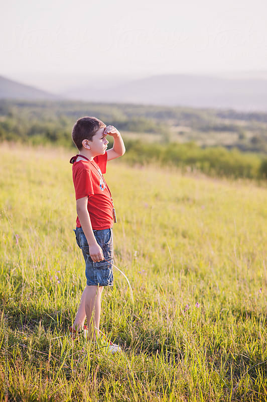 Boy standing on a field and looking at the distance at sunset by Lea Csontos for Stocksy United