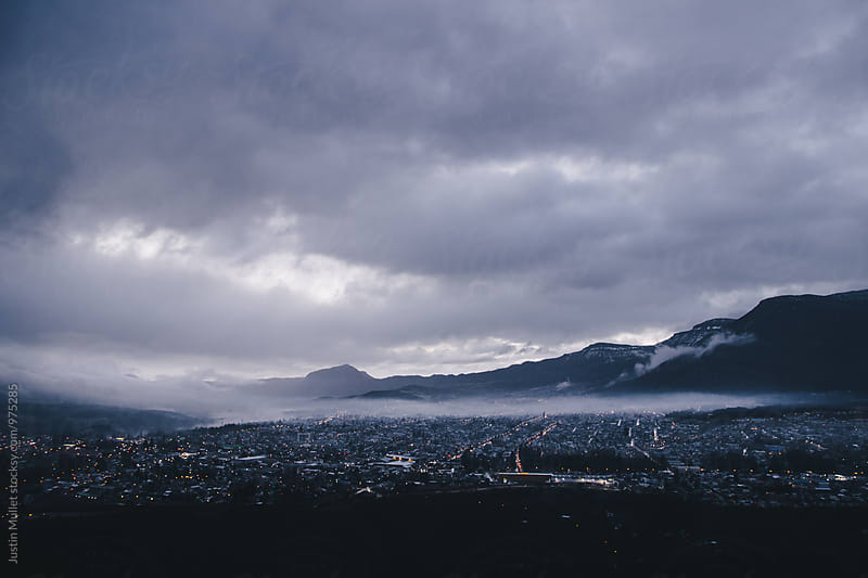 Dawn light over a city near the mountains by Justin Mullet for Stocksy United
