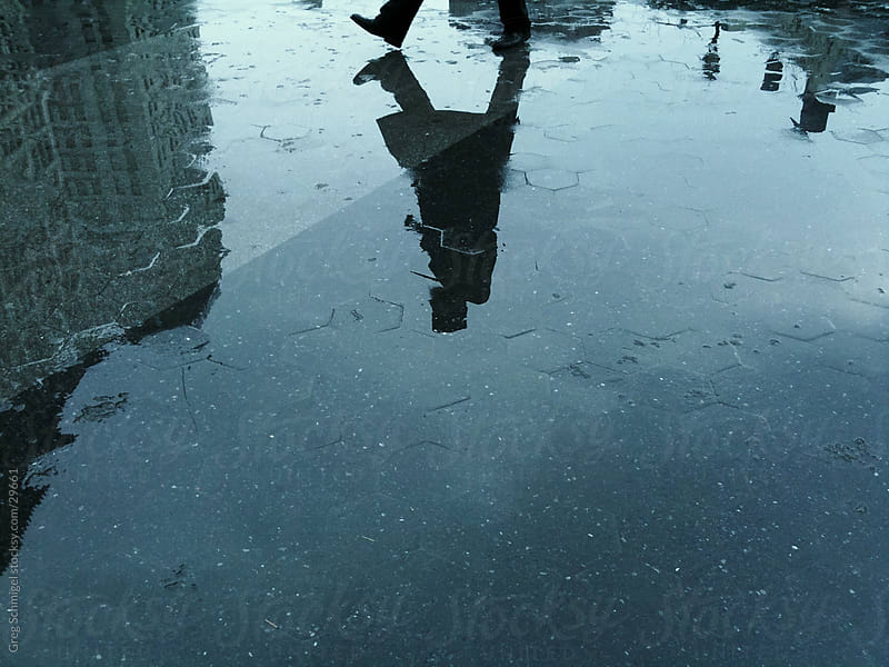 Man walking in rain reflection by Greg Schmigel for Stocksy United