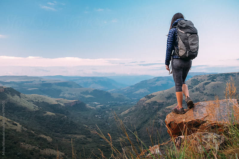 Hiker on a rocky outcrop overlooking a scenic valley by Micky Wiswedel for Stocksy United