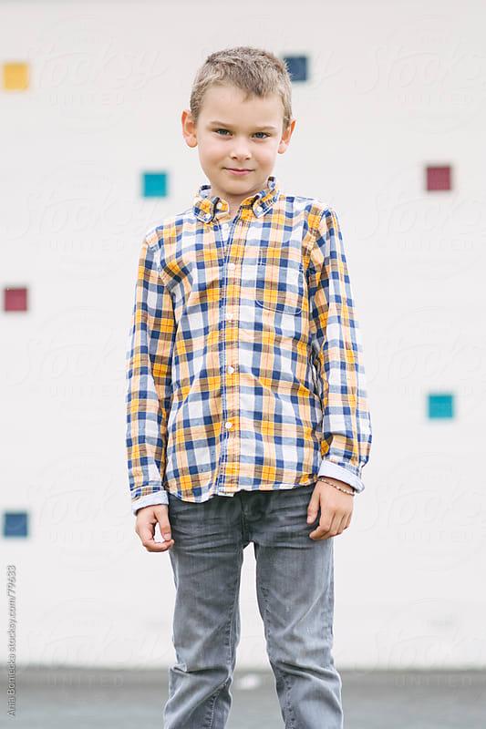 A portrait of a young boy in a plaid shirt by Ania Boniecka for Stocksy United