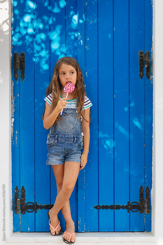 Child and a lolly pop by Dejan Ristovski for Stocksy United