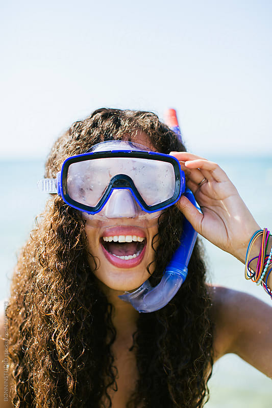 Portrait of a woman with a diving mask on the beach.  by BONNINSTUDIO for Stocksy United