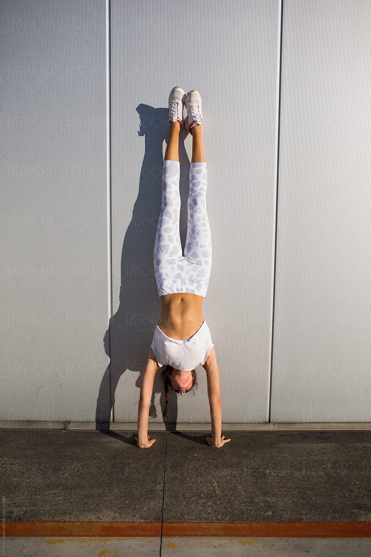 Girl doing handstand by michela ravasio - Stocksy United