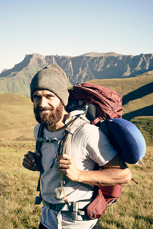 Portrait of a bearded male with his back pack surrounded by mountains. by Jacques van Zyl for Stocksy United