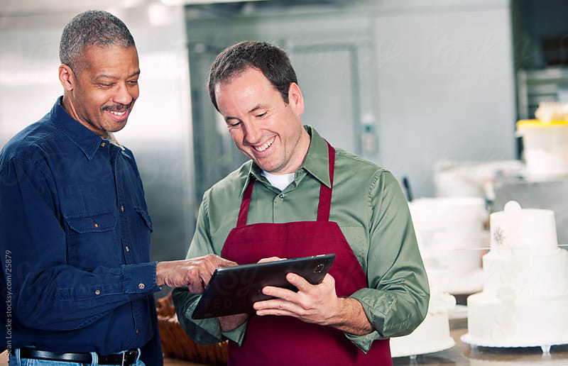 Bakery: Man Showing Bakery Samples to Customer on Digital Tablet by Sean Locke for Stocksy United