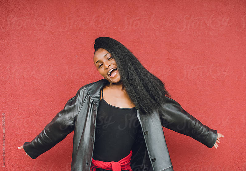 Portrait of happy young woman against red wall by Lauren Naefe for Stocksy United
