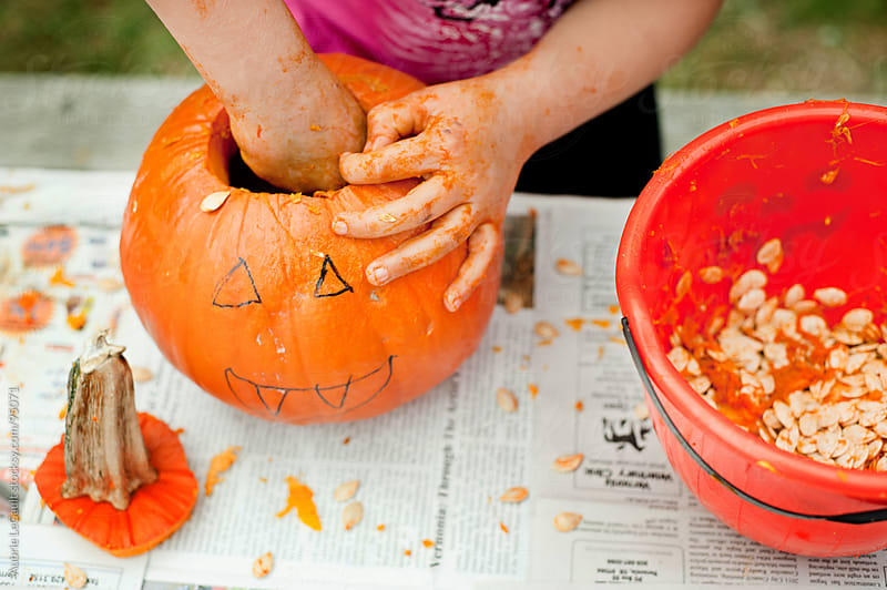 Kid Carving Pumpkin by Aubrie LeGault for Stocksy United
