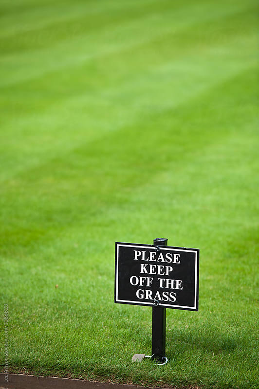 a sign in the lawn reading keep off the grass by Lee Avison for Stocksy United