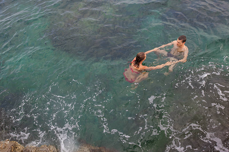 Couple Swimming in the Ocean by Mosuno for Stocksy United