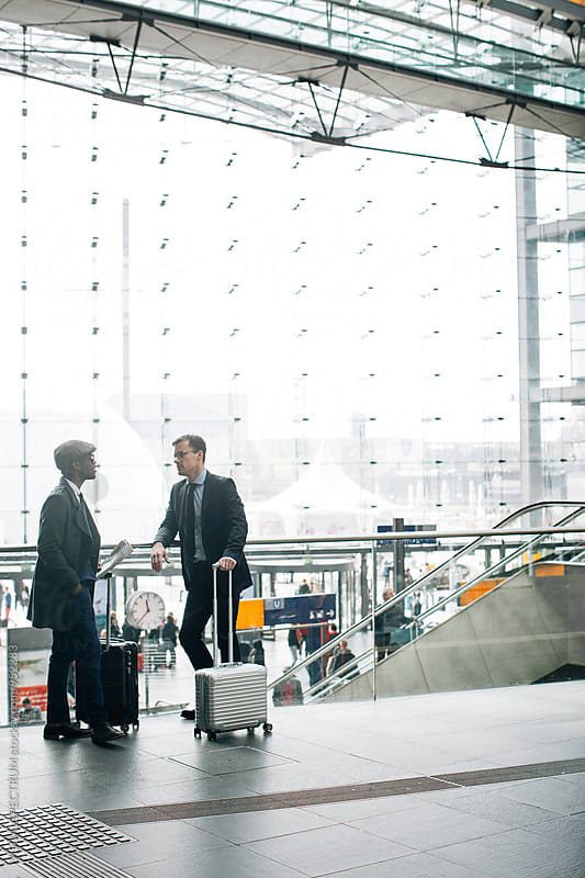 Two Male Business Travelers Chatting and Waiting in Bright Modern Glass Structure by VISUALSPECTRUM for Stocksy United