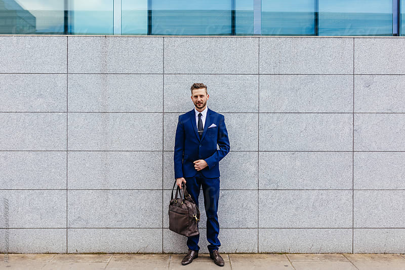Portrait of a young businessman holding his briefcase standing on the street. by Mattia Pelizzari for Stocksy United