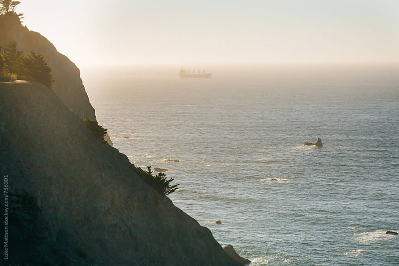 Freight Ship In Distant Fog Seen Over Ocean Cliff Outside San Francisco Bay by Luke Mattson for Stocksy United