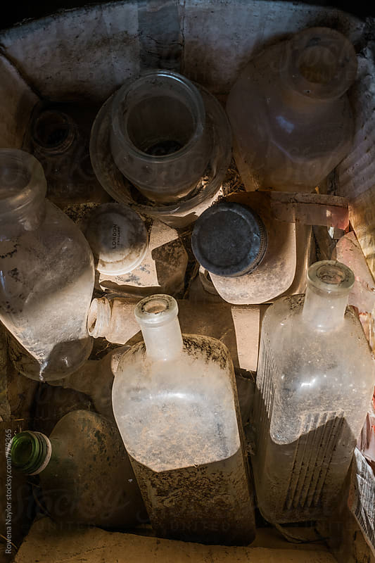 Dusty glass bottles in old farm shed by Rowena Naylor for Stocksy United