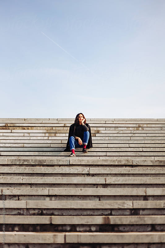 Young woman sitting on the stairs - vertical by Marija Kovac for Stocksy United