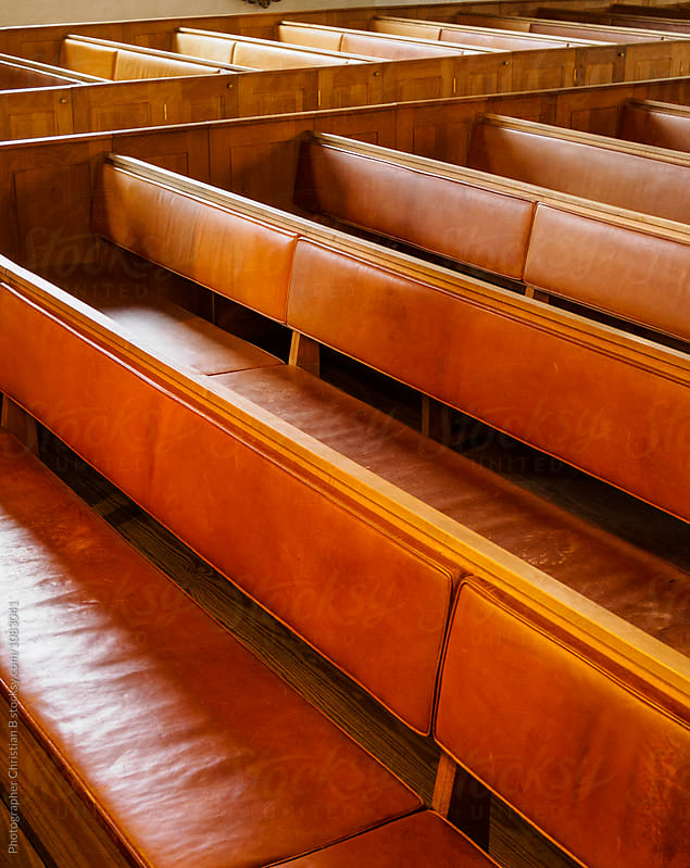 Leather clad benches in a church by Photographer Christian B for Stocksy United