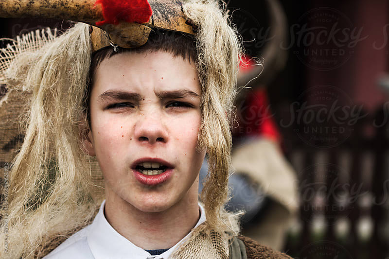 Portrait of young boy in old Slavic dress with traditional mask/Central Serbia by Marko Milanovic for Stocksy United