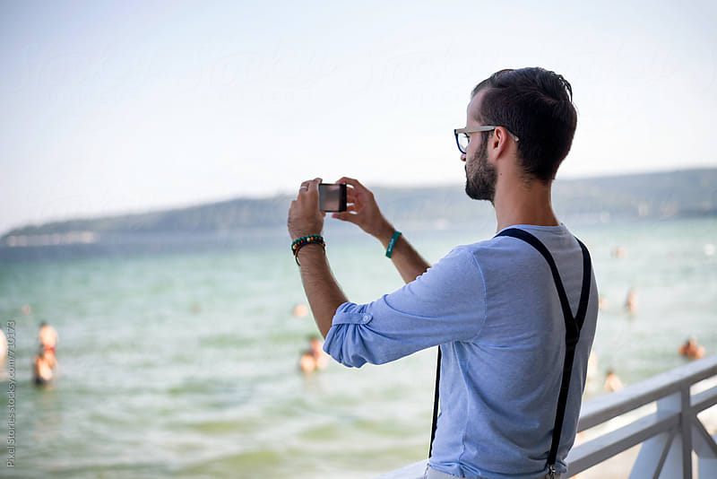 Young man taking photo with his smartphone at the beach by Pixel Stories for Stocksy United
