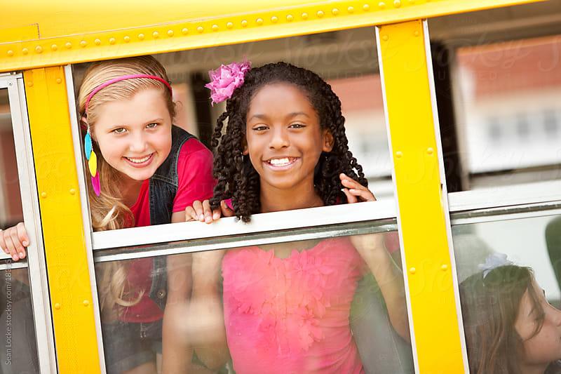 School Bus: Friends Look Out Bus Window by Sean Locke for Stocksy United