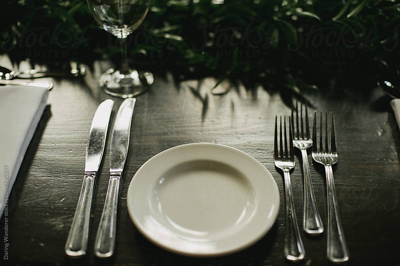 Place setting on wood table with green vine centre piece for holidays by Daring Wanderer for Stocksy United