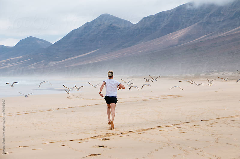 Young man running with birds in a paradisiacal beach by Susana Ramírez for Stocksy United