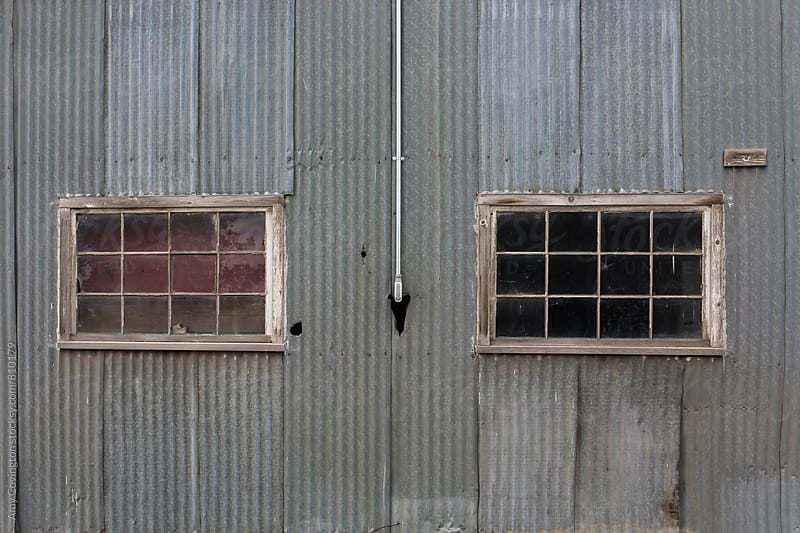 corrugated metal building with two windows by Amy Covington for Stocksy United