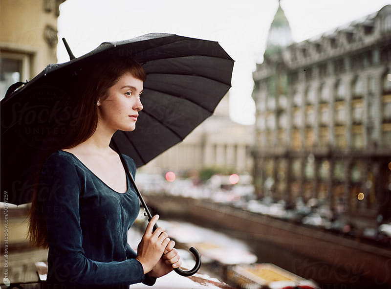 Young woman with umbrella by Lyuba Burakova for Stocksy United