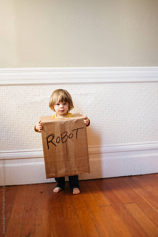 Young child stands in a homemade robot costume. by Lucas Saugen for Stocksy United