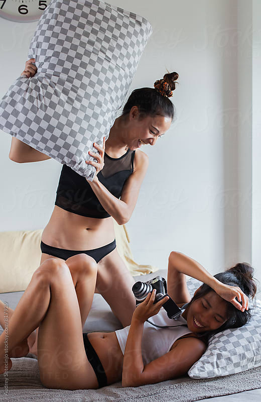 Two girlfriends having fun/pillow fight on bed. by Audrey Shtecinjo for Stocksy United