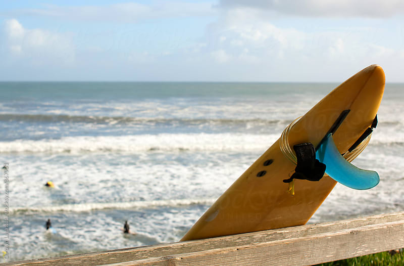Yellow surfboard leaning on a fence with the Pacific ocean and surfers in the background by Carolyn Lagattuta for Stocksy United