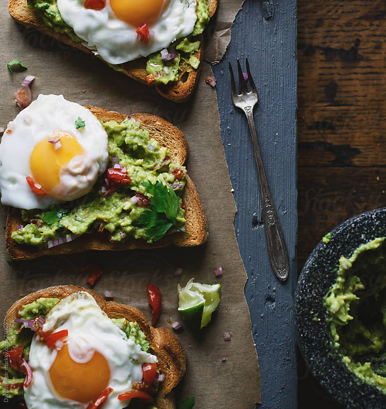 Avocado and fried eggs on toast snack. by Darren Muir for Stocksy United