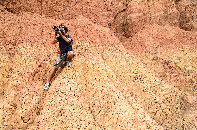 Photographer taking photo while standing in almost vertical sand rock wall by Alice Nerr for Stocksy United