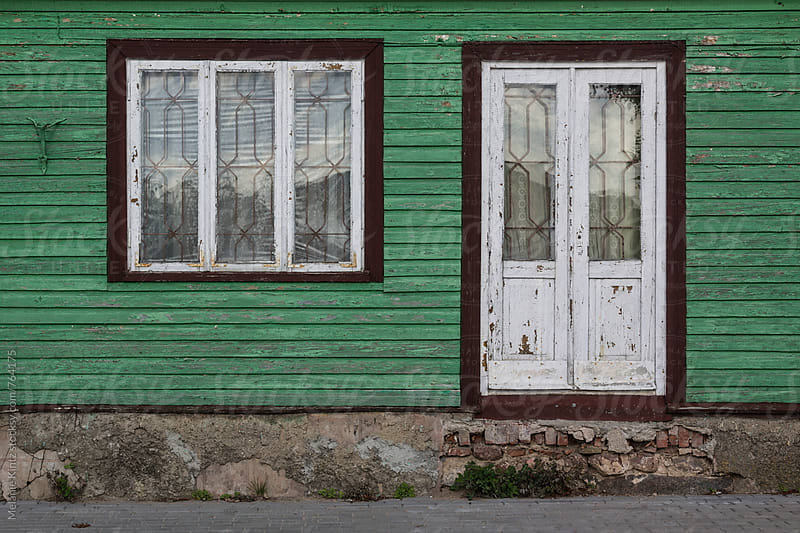 Door and window in green wooden house by Melanie Kintz for Stocksy United