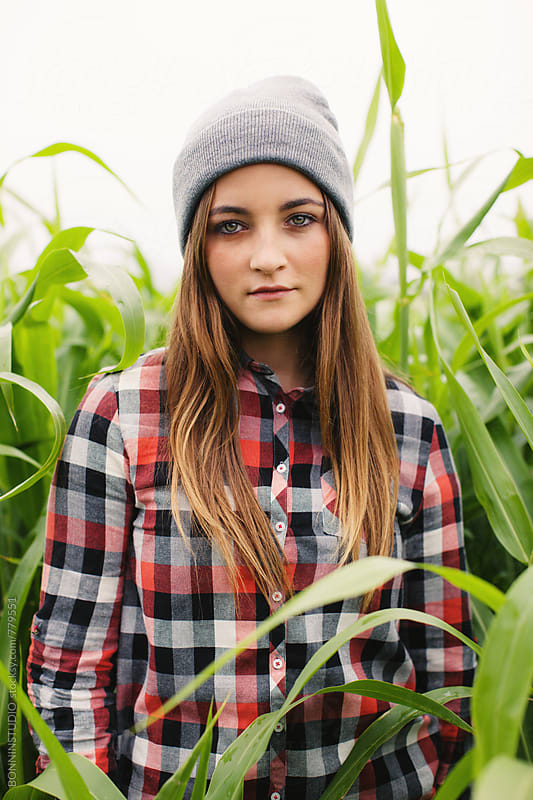 Portrait of a teen girl standing in a corn fields. by BONNINSTUDIO for Stocksy United