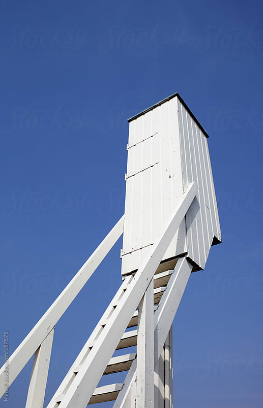 Strange elevated toilet building, against blue sky by Marcel for Stocksy United