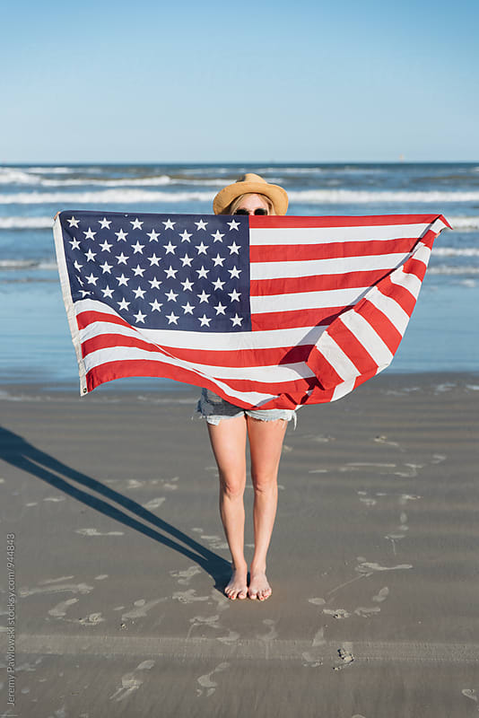 Girl wearing straw hat holding American Flag on the beach. Ocean in back. by Jeremy Pawlowski for Stocksy United
