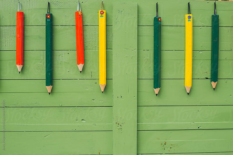 Colourful pencils hanging on a green wall by Jovo Jovanovic for Stocksy United