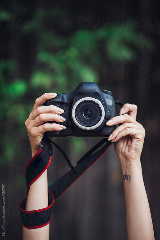 Female photographer holding a camera outdoors by Maja Topcagic for Stocksy United