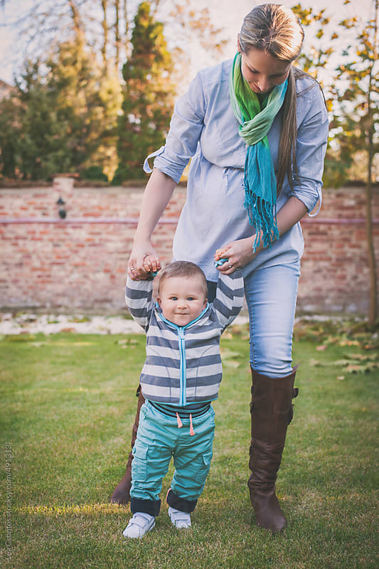 Toddler boy learning to walk with his mother helping him by Lea Csontos for Stocksy United