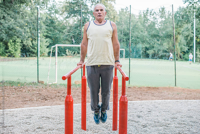 Middle-aged Man Doing Exercise in the Park by Aleksandra Jankovic for Stocksy United