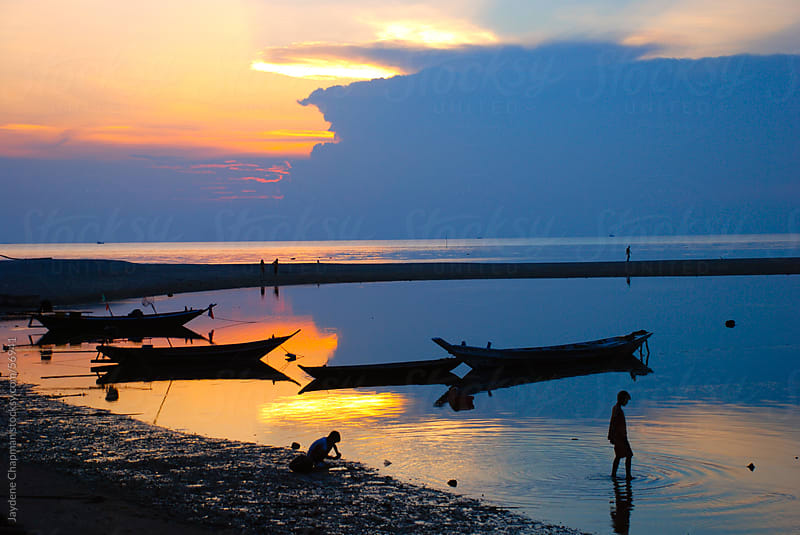 Local children playing in the water near fishing boats at sunset, Thailand by Jaydene Chapman for Stocksy United