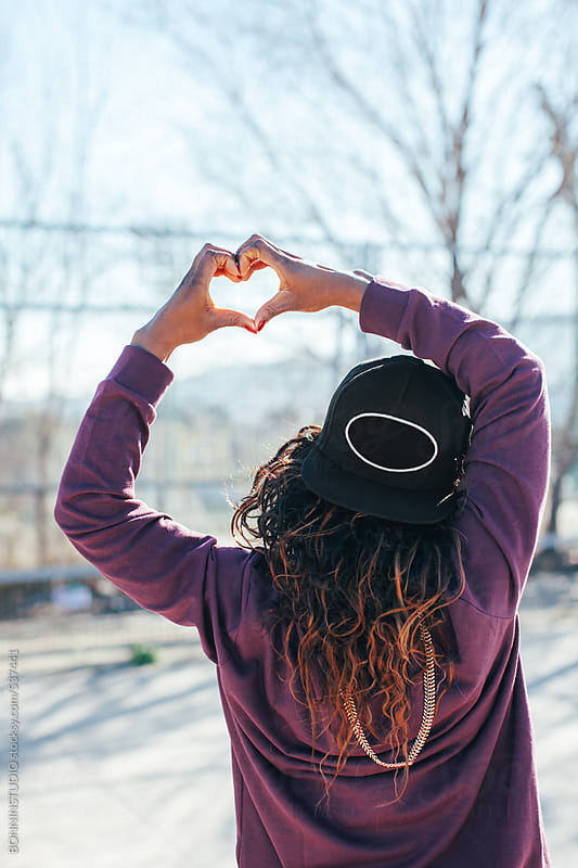 Back view of a hip-hop style woman doing a heart sign with her hands.  by BONNINSTUDIO for Stocksy United