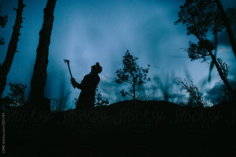 one adult male chops fire wood with an axe at dusk in the forest by LORE for Stocksy United
